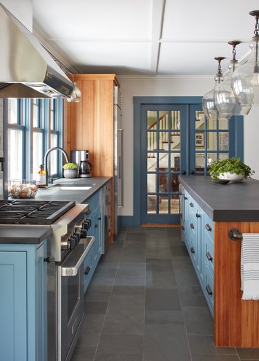 pale blue kitchen with wood accents and grey countertops