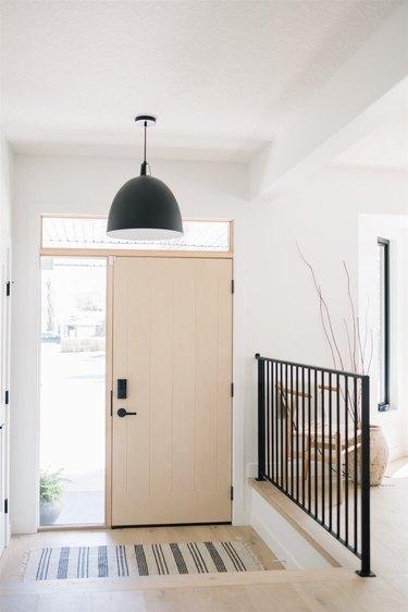 minimalist entryway with large black pendant light and black railing