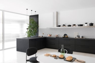 black kitchen accent wall behind tree with black cabinets