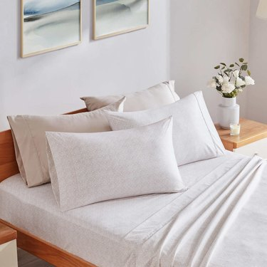 Cream sheets on a bamboo bed with flowers on the bedside table.