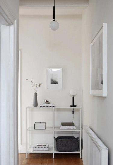 minimalist hallway with hanging light and framed artwork