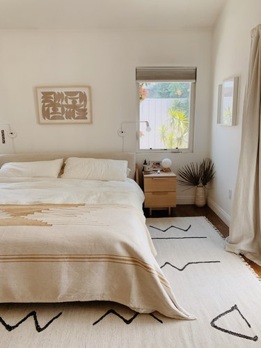 minimalist bedroom with geometric area rug and white walls