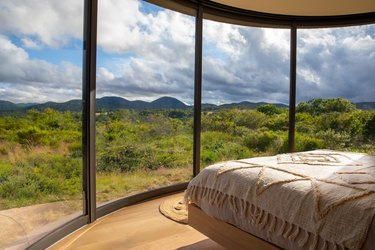 view from inside dome shaped space looking out into natural landscape with clouds