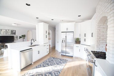 open kitchen with brick wall and white cabinetry