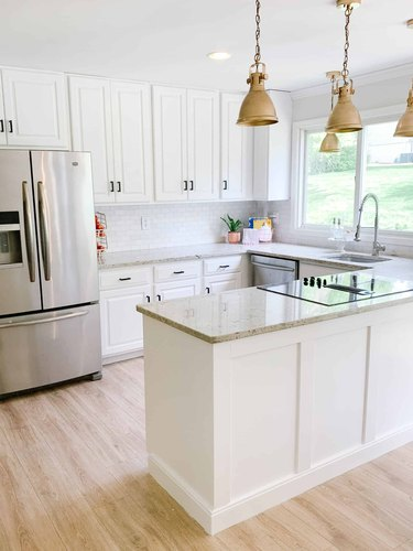 open kitchen with u-shaped layout and brass pendants
