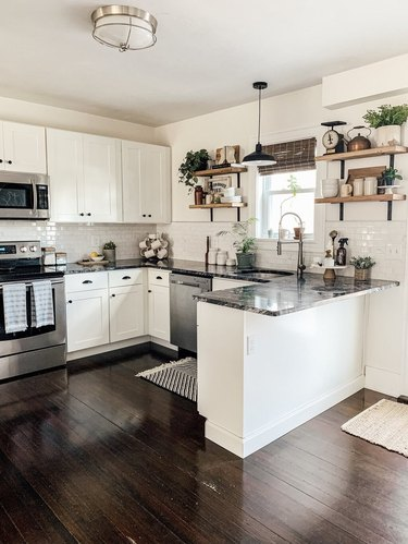 open kitchen with u-shaped layout and dark wood flooring