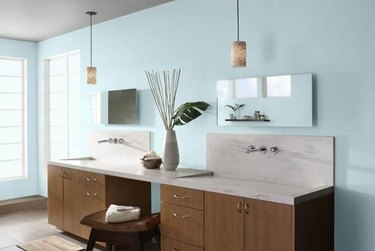 bathroom  with two sinks and light blue walls and stool