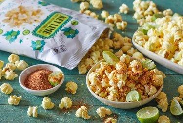 kettle corn bag with kettle corn and plates and lime on green surface