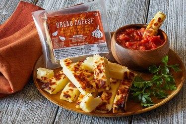 plate with garlic bread cheese, greens, and a bowl with marinara