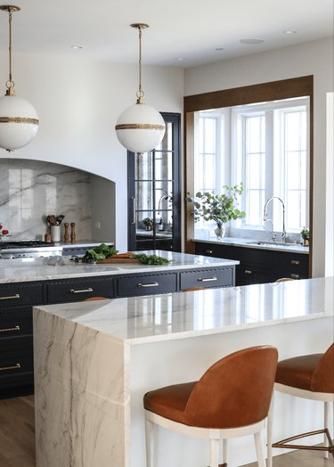 open kitchen with marble countertops and oversized pendants