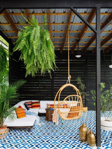 black painted outdoor patio with blue rug, trailing plants, and hammock seat