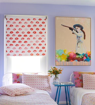 bedroom with red lip patterned curtain and two beds and artwork showing a person holding a gun