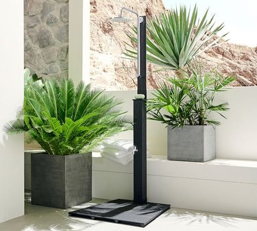 A freestanding outdoor shower near concrete planters in a backyard alcove