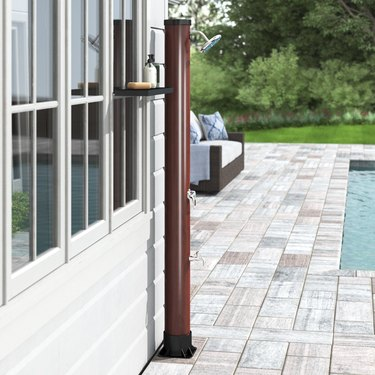 A freestanding outdoor shower by a backyard pool