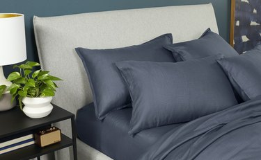 bed with blue sheets and table with lamp on the side