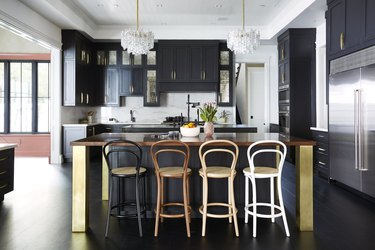 kitchen with black cabinets and thonet bar stools