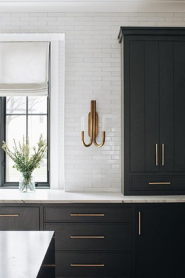 brass wall sconce in traditional kitchen with black kitchen cabinets