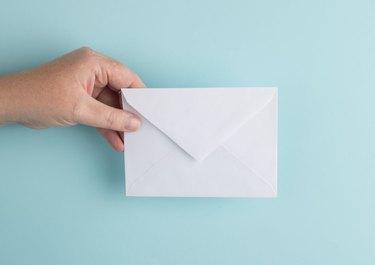 person holding envelope over light blue background
