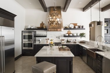 large traditional kitchen with black cabinets and copper details