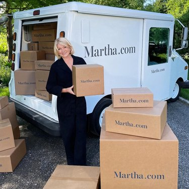 """Martha Stewart standing with boxes near a white mail truck that reads """"Martha.com"""""""