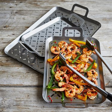 three steel grill grids, one with shrimp and tongs