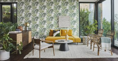 Yellow couch in wallpapered living room