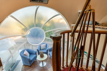 interior of The Bubble House showing a round window and blue chairs near table