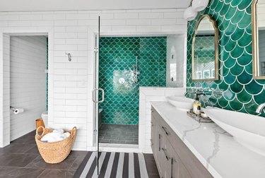 Bathroom with green tile backsplash, white sink area, green tile shower.