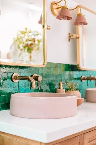 Pink vessel sink, green mosaic backplash, brass faucets.