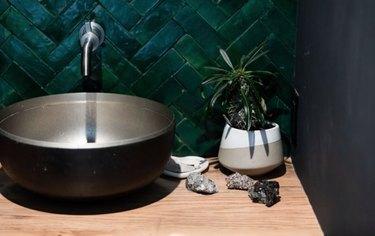 Metal vessel sink with matte green tile backsplash.