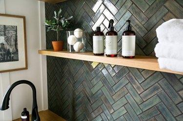 Bathroom with matte green tile backsplash, open shelf, black faucet.