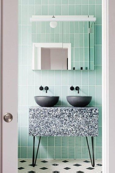 Mid-century modern bathroom with green tile wall, marble vanity, black vessel sinks.