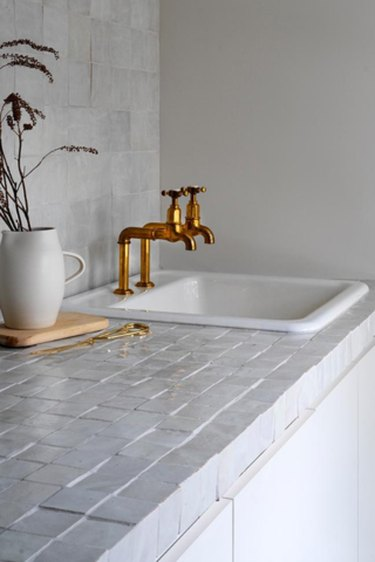 gray zellige tile and brass faucets