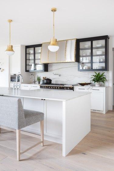 black and white kitchen with marble slap backsplash