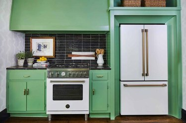 green kitchen with white appliances and black tile