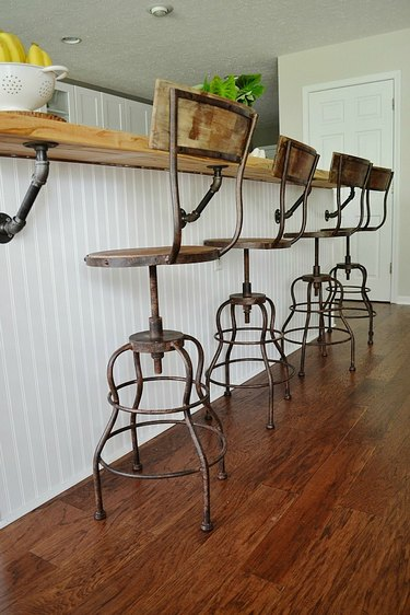 rusted bar stools and white island in industrial kitchen
