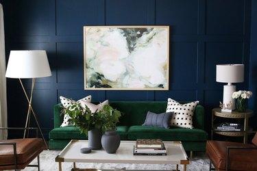 navy blue wall with emerald green velvet sofa
