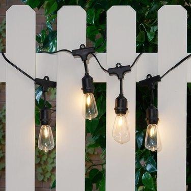 String lights on white picket fence
