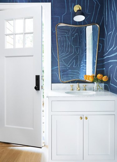 navy blue and white powder room with patterned wallpaper