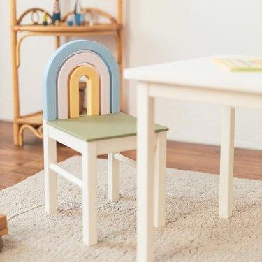 kids' rainbow chair next to white table