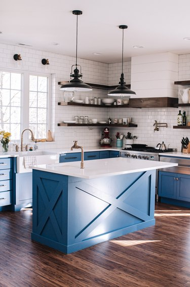industrial kitchen with blue cabinetry and white backsplash