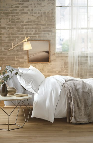 White bedding on bed with brick wall behind