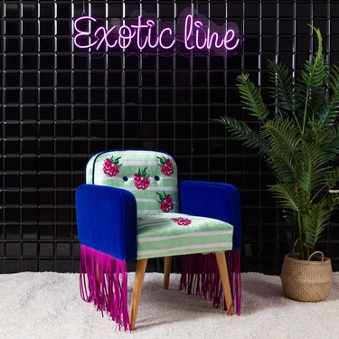 """black tiled wall with neon sign that read """"exotic line"""" and embroidered chair with fringe"""