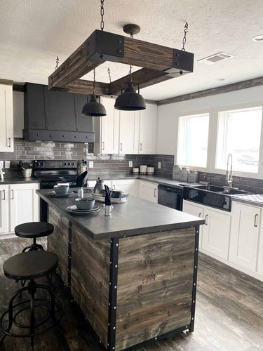 industrial kitchen with wood and black island and hanging lights