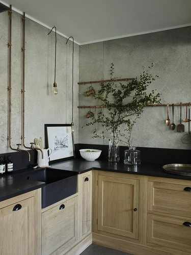 industrial kitchen with exposed copper pipes on wall
