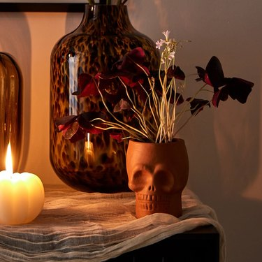 table with vase, candle, and terracotta skull vase with flowers