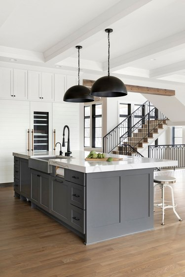 industrial kitchen with gray island and oversized pendants