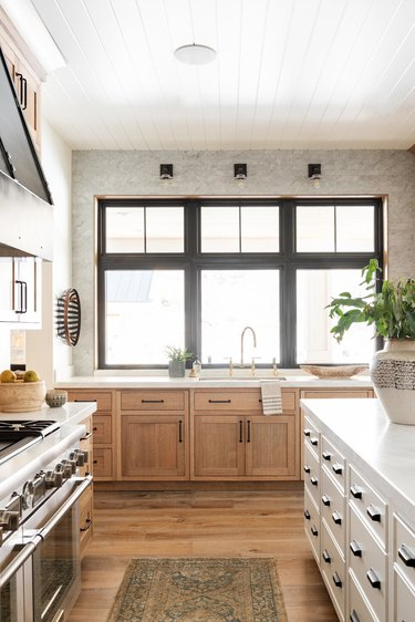 industrial kitchen with black sconces and light wood cabinets