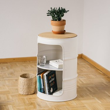 night stand made from small oil drums in white color with books and plant on top