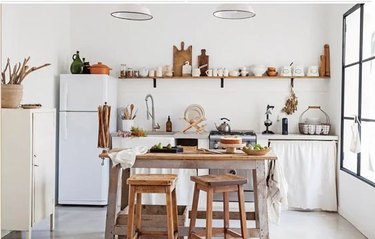 Minimalist white kitchen with linen cabinet curtains and open shelving.